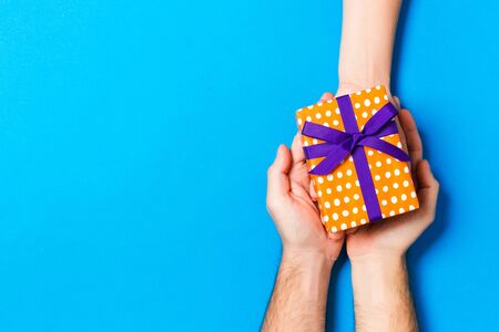 Top view of a woman and a man giving and receiving a present on colorful background. Love and relationship concept. Copy space.
