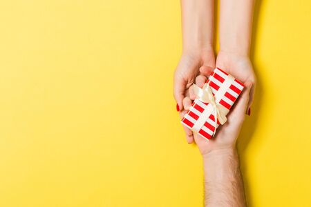 Top view of a man and a woman congratulating each other with a gift on colorful background. Surprise for a holiday concept. Close up.
