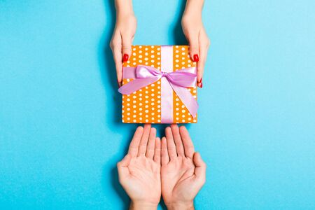Top view of couple giving and receiving a gift on colorful background. Close up of romantic concept.