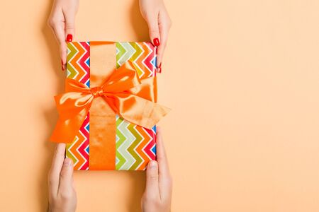 Top view of male and female hands holding present box on colorful background. Sharing a gift concept. Copy space.