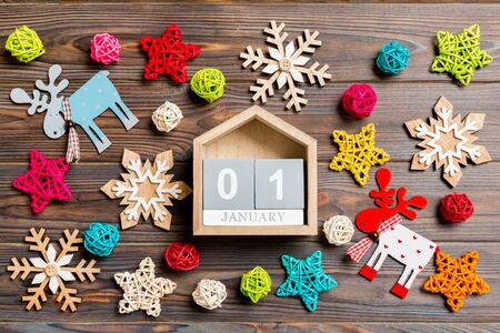 Top view of calendar on Christmas wooden background. The first of January. New Year toys and decorations. Holiday concept. Stock Photo