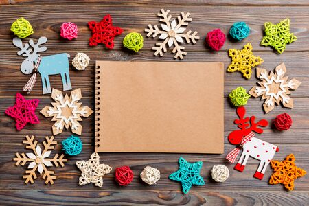 Top view of notebook on wooden background made of Christmas decorations. New Year concept. Stock Photo