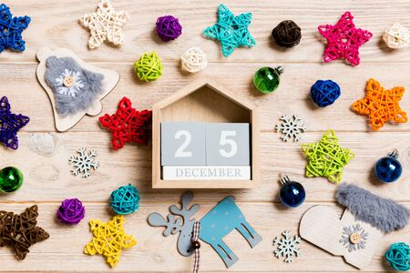 Top view of calendar on Christmas wooden background. The twenty fifth of December. New Year toys and decorations. Holiday concept.