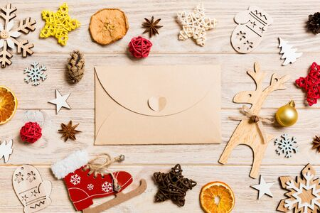 Top view of envelope on festive wooden background. Christmas toys and decorations. New Year time concept.