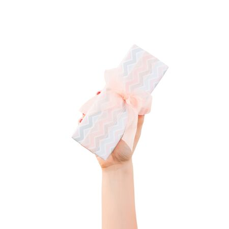 Woman hands give wrapped Christmas or other holiday handmade present in colored paper with orange ribbon. Isolated on white background, top view. thanksgiving Gift box concept. Stock Photo