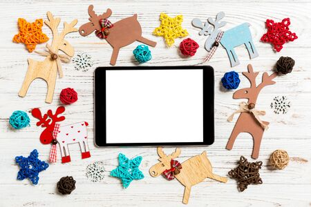 Top view of tablet on holiday wooden background. New Year decorations and toys. Christmas concept.