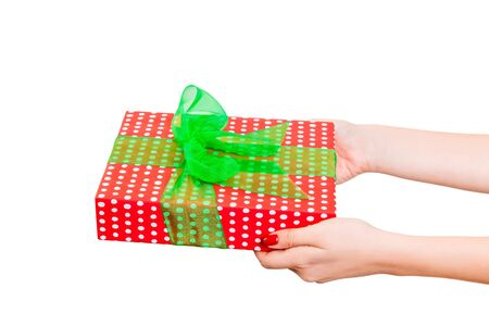 Woman hands give wrapped Christmas or other holiday handmade present in red paper with Green ribbon. Isolated on white background, top view. thanksgiving Gift box concept.