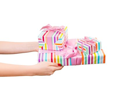 Woman hands give wrapped group of Christmas or other holiday handmade present in colored paper with pink ribbon. Isolated on white background, top view. thanksgiving Gift box concept. Stok Fotoğraf