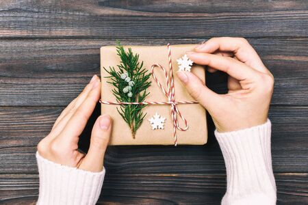 A woman hand holding christmas gift box on hand, on dark wooden background. top view with copy space. Toned.