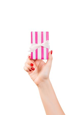 Woman hands give wrapped Christmas or other holiday handmade present in pink paper with white ribbon. Isolated on white background, top view. thanksgiving Gift box concept. Stok Fotoğraf