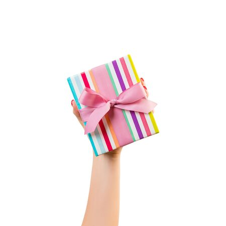 Woman hands give wrapped Christmas or other holiday handmade present in colored paper with pink ribbon. Isolated on white background, top view. thanksgiving Gift box concept. Stok Fotoğraf