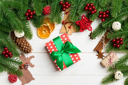 Top view of fir tree branches, gift and festive decorative toys on wooden background. New Year time concept.