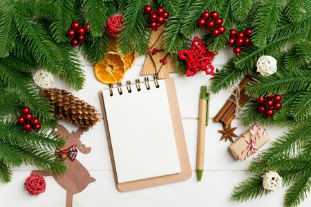 Top view of fir tree branches, notebook and festive decorative toys on wooden background. New Year time concept.