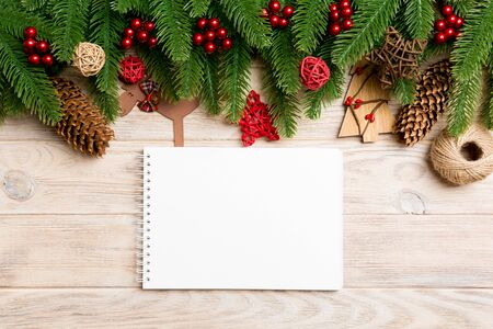 Top view of notebook, Christmas toys, decorations and fir tree branches on wooden background. New Year holiday concept.