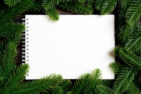Top view of notebook decorated with a frame made of fir tree on wooden background. New Year time concept. 写真素材