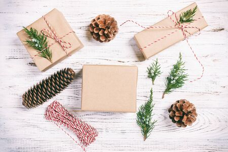 Hand crafted gift box on rustic white wooden background with Christmas decoration fir tree, top view. Toned.