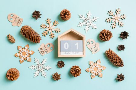 Top view of wooden calendar, holiday toys and decorations on blue Christmas background. The first of January. New Year time concept.