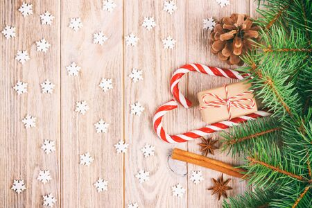 Christmas gift box, candy cane with snowflake and fir tree branch on wooden table. Toned. Zdjęcie Seryjne
