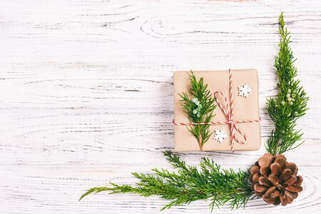 Christmas composition background. Christmas gift with pine cones and fir branches on wooden background. Flat lay, top view, copy space. Toned.
