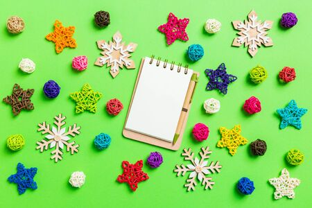 Top view of notebook. New Year decorations on green background. Festive stars and balls. Merry Christmas concept. Фото со стока