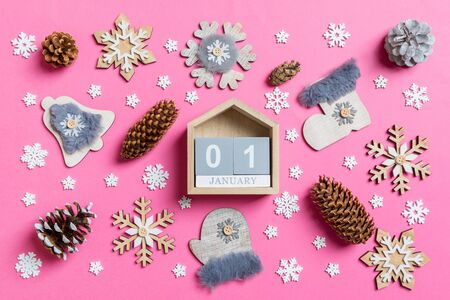Top view of wooden calendar, holiday toys and decorations on pink Christmas background. The first of January. New Year time concept. Stok Fotoğraf