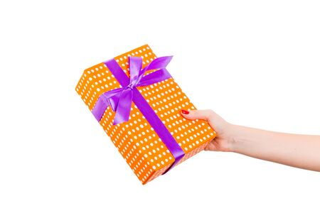 Woman hands give wrapped Christmas or other holiday handmade present in orange paper with purple ribbon. Isolated on white background, top view. thanksgiving Gift box concept.