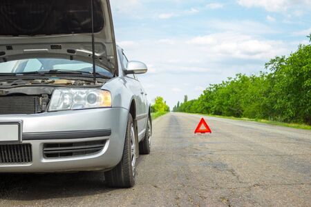 Car with problems and a red triangle to warn other road users.