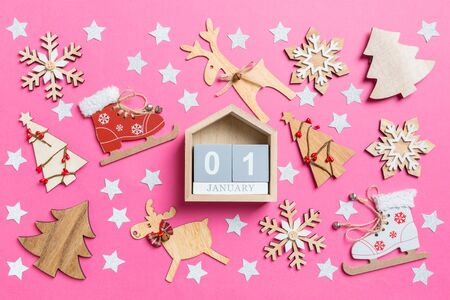 Top view of calendar, pink background decorated with festive toys and Christmas symbols reindeers and New Year trees. The first of January. Holiday concept.
