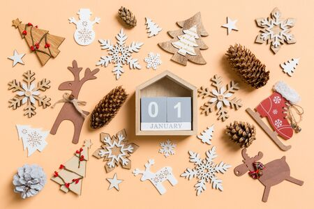 Top view of wooden calendar surrounded with New Year toys and decorations on orange background. The first of January. Christmas time concept.