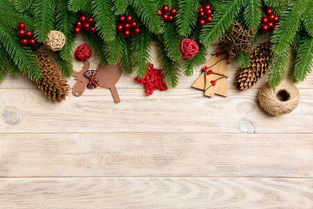 Top view of Christmas toys, decorations and fir tree branches on wooden background. New Year holiday concept with copy space. Stock Photo