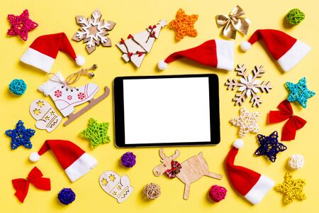 Top view of digital tablet with Christmas decorations and Santa hats on yellow background. Happy holiday concept. Stock Photo