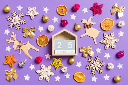 Top view of wooden calendar surrounded with New Year toys and decorations on purple background. The twenty fifth of December. Christmas time concept. Stock Photo