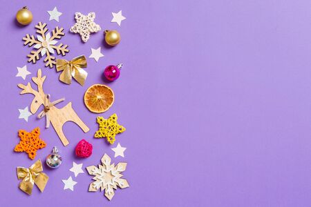 Top view of New Year toys and decorations on purple background. Christmas time concept with empty space for your design.