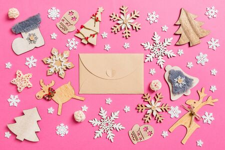 Top view of craft envelope on pink background made of holiday decorations and toys. Christmas ornament concept.
