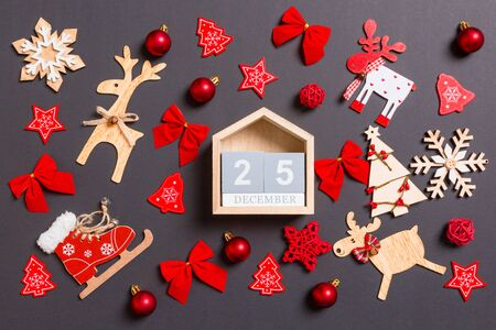 Christmas black background with holiday toys and decorations. Top view of wooden calendar. The twenty fifth of December. Merry Christmas concept. Stock Photo