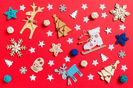 Top view of holiday toys and decorations on red Christmas background. New Year time concept.