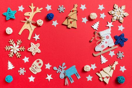 Top view of holiday toys and decorations on red Christmas background. New Year time concept with copy space.