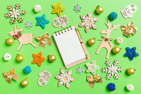 Top view of notebook on green background with New Year toys and decorations. Christmas time concept.