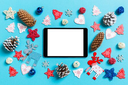 Top view of digital tablet surrounded with New Year toys and decorations on blue background. Christmas time concept.