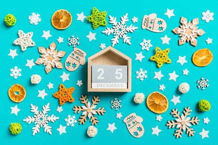 Top view of wooden calendar on blue background with New Year toys and decorations. The twenty fifth of December. Christmas time concept.