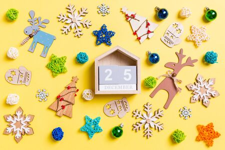 Top view of wooden calendar on yellow background with New Year toys and decorations. The twenty fifth of December. Christmas time concept.