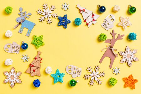 Top view of yellow background with New Year toys and decorations. Christmas time concept with copy space.