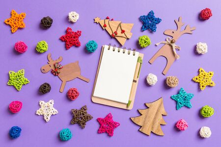 Top view of notebook. New Year decorations on purple background. Festive stars and balls. Merry Christmas concept.