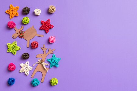 New Year decorations on purple background. Festive stars and balls. Merry Christmas concept with empty space for your design.