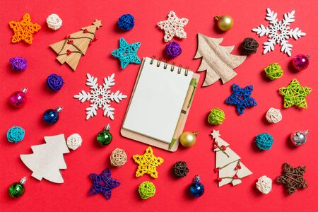 Top view of notebook on red background made of holiday decorations and toys. Christmas ornament concept.