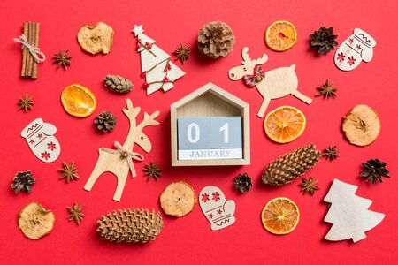 Top view of calendar, red background decorated with festive toys and Christmas symbols reindeers and New Year trees. The first of January. Holiday concept.