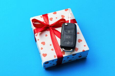 Car key on paper gift box with red ribbon bow and heart on blue table background. Holidays present top view concept. Reklamní fotografie