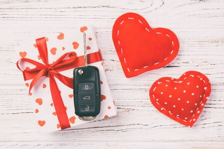 Valentine or other holiday handmade present in paper with red hearts, car keys and gifts box in holiday wrapper. box gift on white wooden table top view with copy space, empty space for design.