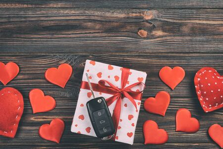 Valentine or other holiday handmade present in paper with red hearts, car keys and gifts box in holiday wrapper. box gift on Farkwooden table top view with copy space, empty space for design.