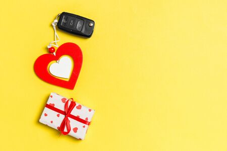 Top view of gift box, car key and wooden heart on colorful background. Luxury present for Valentine's day.